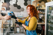Beautiful and positive redhead ginger woman smiling and working in handmade ice cream store. She preparing and serving delicious sweet food.
