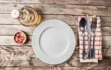 Vintage Table Setting With Napkin, Fork, Knife And Plate On Old Rustic Wooden Table