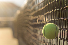 Close-up Of Tennis Ball By Net At Court