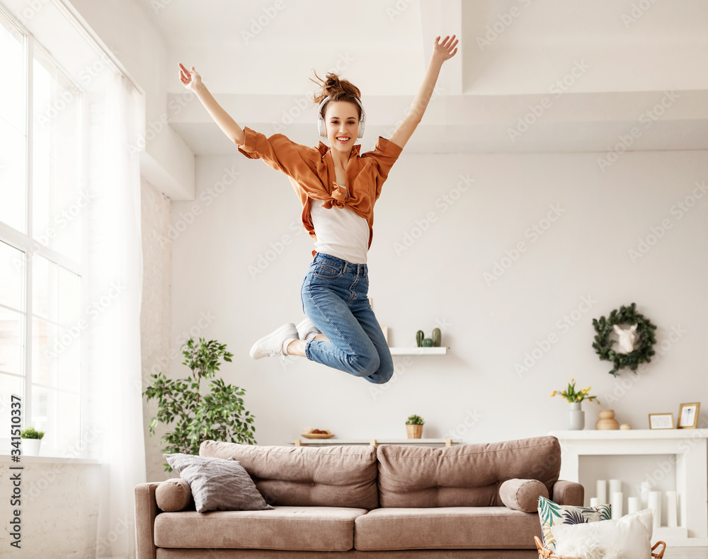 Fototapeta Excited millennial woman listening to music and having fum at home.