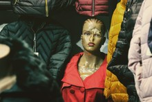Old Weathered Mannequin Wearing Red Jacket By Winter Coats In Store