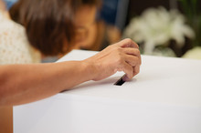 Cropped Hand Of Woman Casting Vote In Ballot Box