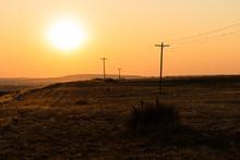 Blazing Hot Sun Over A Western Desert Terrain With Telephone Poles