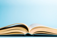 Close-up Of Open Book On Table Against Blue Background