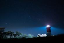 Lighthouse On Field Against Sky At Night