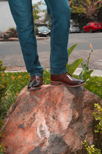 Outdoor Photo Of A Man With Brogue Shoes Standing On A Rocky Boulder