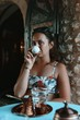 Portrait Of Woman Drinking Coffee While Sitting In Cafe