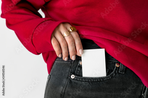 Woman keeping a white card in a pocket of her jeans Canvas Print