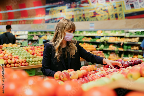Tela Woman in a face mask while shopping in a supermarket during coronavirus quaranti