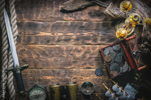 Fototapeta Pirate treasure chest with ancient coins and other various pirate equipment on flat lay table background