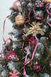 Balls ribbon garlands in pink gold maroon style close up on artificial Christmas tree decorations. Cones in gold silver glitter sequins on Christmas tree. Texture of a Christmas tree