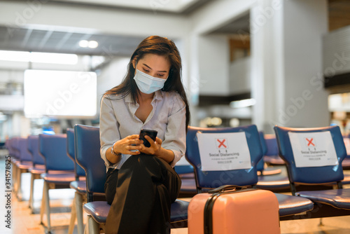 Obraz Young Asian tourist woman with mask using phone and sitting with distance at the airport - fototapety do salonu