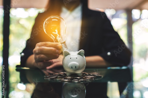 Fototapeta A businesswoman putting light bulb over a piggy bank on pile of coins on the tab