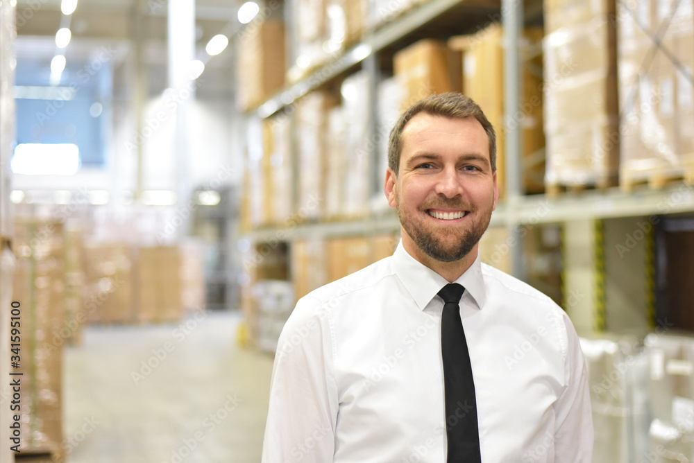 Fototapeta portrait friendly businessman/ manager in suit working in the warehouse of a company