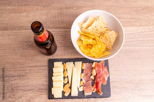 Obraz na plátne Small cheese platter with Serrano ham and Iberian loin with chips and beer