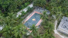 Drone Aerial View Flying Over A Basketball Court With A Group Of Young Men Playing Basketball Surrounded By  An Exottic Location In Asia Philippines With Tall Palm Trees In The Philipines