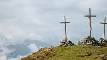Timelapse Pan Showing Three Large Crucifixes On Top Of A Mountain. Timelapse Of Three Large Christian Crosses Being Held By Large Stone Piles At The Peak Of A Mountain During A Cloudy Day