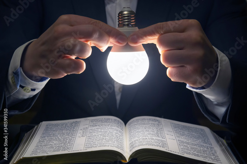 man reads the holy bible in the light of the LED lamp on. the search for God and the study of the book. Christianity and religion