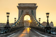 Hungary Budapest. Szechenyi Chain bridge with sunrise. Bright golden light and rising sun. Nobody in streets. Emptyness for reason of coronavírus.