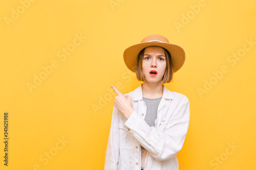 Surprised pretty girl in light summer dress and hat isolated on yellow background, looks into camera with emotionless face and points finger towards empty space Slika na platnu