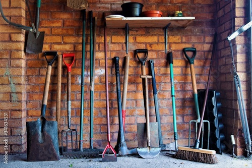 Light falls on an armoury of well used garden tools. Canvas Print