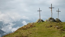 Timelapse Of Three Large Crucifixes On Top Of A Mountain. 4K UHD Time Lapse Showing Three Large Christian Crosses Being Held By Large Stone Piles At The Peak Of A Mountain During A Cloudy Day