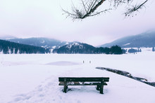Wooden Bench On Snow Covered Field Against Sky
