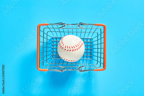 Baseball ball in metal market basket on blue background. Purchasing sport accessories. Concept of corruption in sport