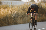 Active professional sportsman cyclist wearing black sports outfit, helmet and glasses riding bike at the paved road outdoors. Strong man improving skills and getting ready for cycling competition