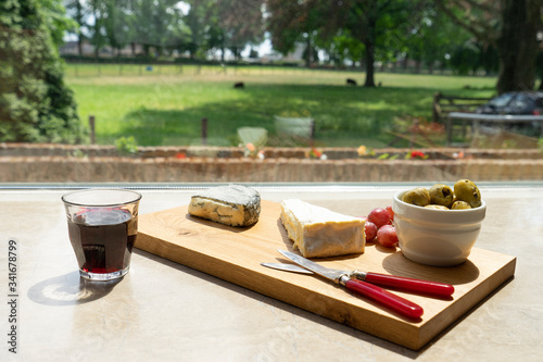 A wooden board with cheese olives tomatoes and wine in front of a window with view on the garden