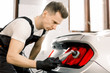 Car detailing series, polishing concept. Professional Caucasian male auto service worker, wearing black protective gloves, waxing and polishing tail light of luxury white car with polish machine