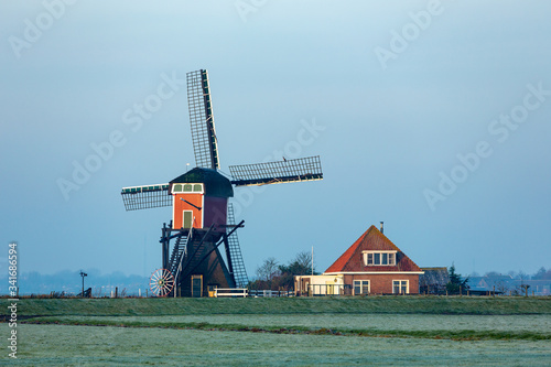 Photo The back of the Red Mill in the grasslands of the South Holland villag of Oud Ade