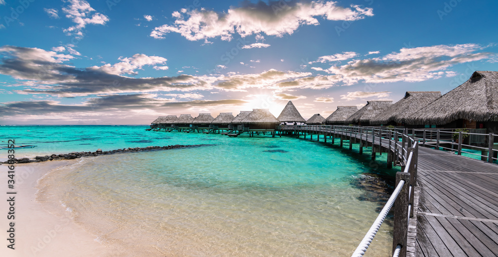 Fototapeta Scenic panoramic landscape view of  luxury overwater bungalows at the beach and lagoon during sunset in Moorea, French Polynesia.