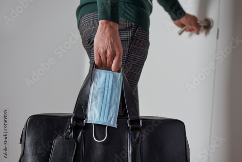 Fotografiet man with a suitcase and a surgical mask