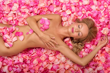 Panel Szklany Do Spa Beautiful slim young woman lying on petals of pink roses. Perfect figure.