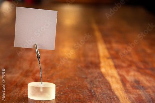 Fototapeta biglietto in bianco su un tavolo in legno