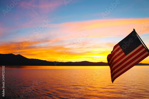 American Flag Over Lake Against Sky During Sunset Billede på lærred