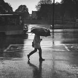 Side View Of Man Walking With Umbrella On Road