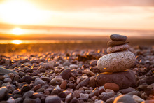 Stack Of Pebbles At Beach During Sunset