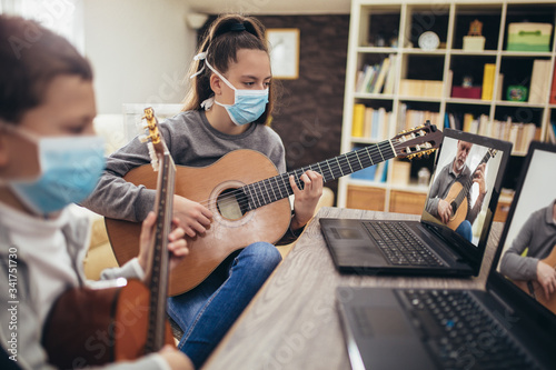 Obraz Boy and girl, wear protective masks, playing acoustic guitar and watching online course on laptop while practicing at home. Online training, online classes. - fototapety do salonu