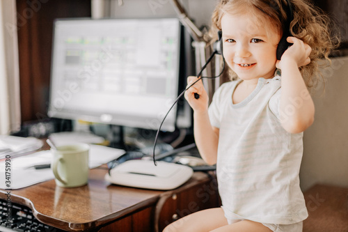 Photo little girl with headphones sitting at mom's computer who is forced to work at h