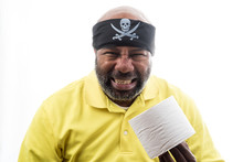 African American Man With Toilet Paper And Pitate Bandanna.  COVID 19 Concept Of Lockdown, Flatten The Curve, Social Distancing, State Of Emergency, Corona Virus.