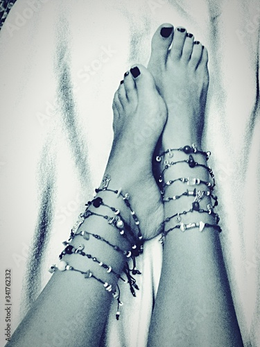 Photo Low Section Of Woman Wearing Anklets Resting On Bed