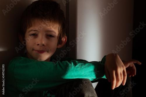 Fotografía portrait of a boy con cara de sueño mitad en sombra y mitad con luz de la Mañana
