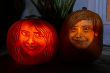 Two Lighted Jack-o-lantern Pumpkins Carved With Detailed Faces Of A Girl And A Boy For Halloween