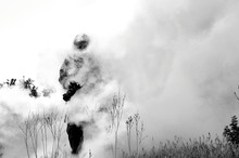 Man Holding Camera While Walking On Field During Foggy Weather