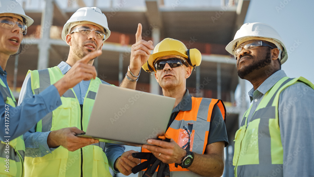 Fototapeta Diverse Team of Specialists Use Laptop Computer on Construction Site. Real Estate Building Project with Civil Engineer, Architectural Investor, Businesswoman and Worker Discussing Blueprint Plan