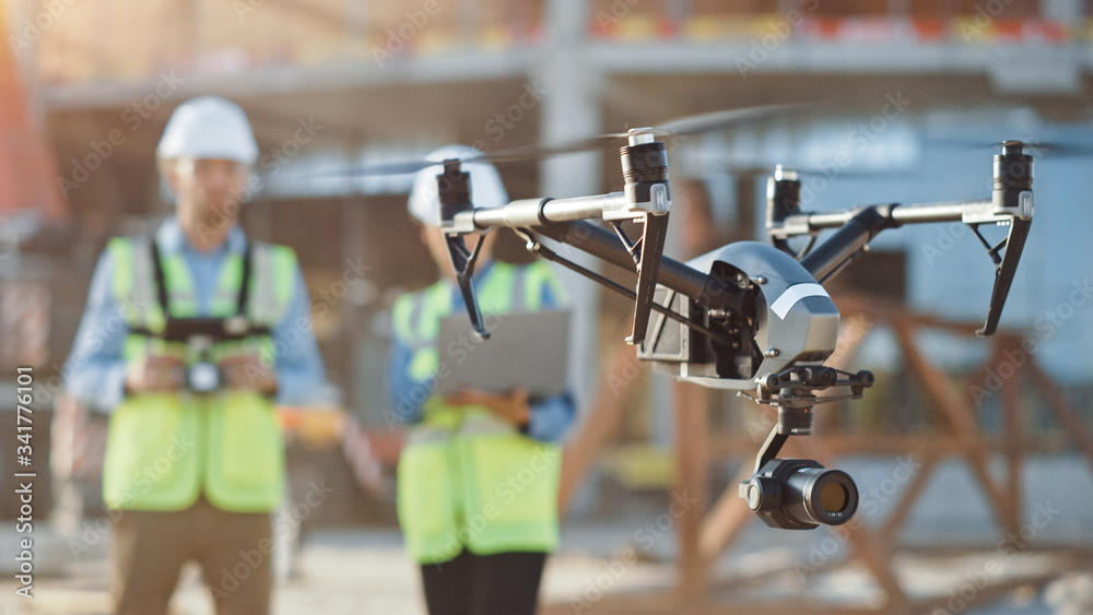 Fototapeta Two Specialists Use Drone on Construction Site. Architectural Engineer and Safety Engineering Inspector Fly Drone on Building Construction Site Controlling Quality. Focus on Drone