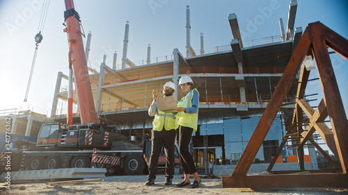 Two Specialists Inspect Commercial, Industrial Building Construction Site. Real Estate Project with Civil Engineer, Investor Use Laptop. In the Background Crane, Skyscraper Concrete Formwork Frames