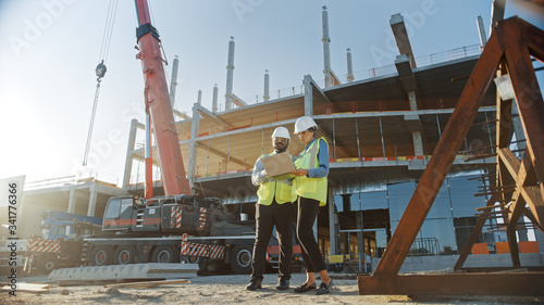 Obraz na płótnie Two Specialists Inspect Commercial, Industrial Building Construction Site
